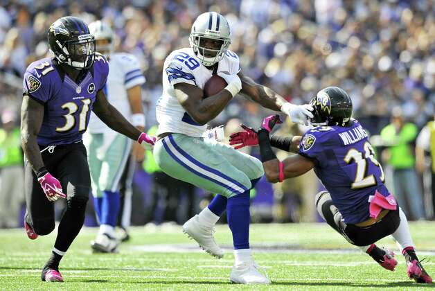 Dallas Cowboys running back DeMarco Murray, center, rushes the ball between Baltimore Ravens strong safety Bernard Pollard, left, and Baltimore Ravens cornerback Cary Williams in the first half of an NFL football game in Baltimore, Sunday, Oct. 14, 2012. (AP Photo/Gail Burton) Photo: Gail Burton, Associated Press / FR4095 AP