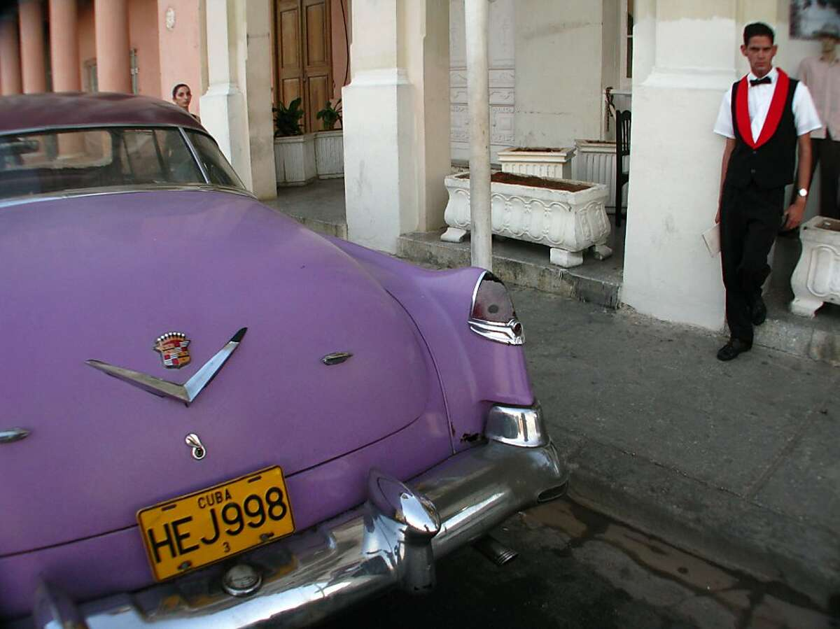 A classic 1950s Caddy sits in front of Cafeteria Prado No. 12 -- mostly to attract clients to the restaurant -- near the tree-lined Prado in Havana, Cuba.