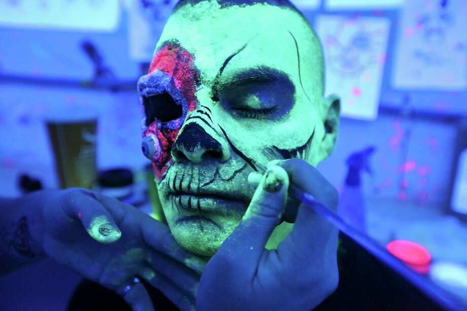 Makeup artist Shauna Burns, 23, applies zombie makeup to actor David Hernandez, 29, under black-light Sunday Oct. 14, 2012 at Nightmare on Grayson. Photo: Edward A. Ornelas, San Antonio Express-News / © 2012 San Antonio Express-News