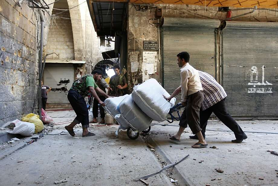 Men remove goods from their shops in Aleppo's souk, days before fighting set the bazaar ablaze. Photo: Hussein Malla, Associated Press