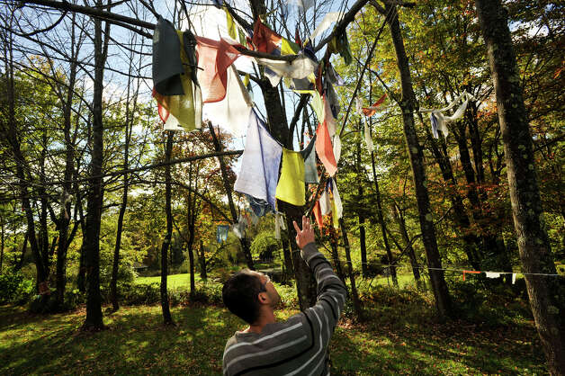 Jampa inspects a prayer flag on the grounds behind the Do Ngak Kunphen Ling Tibetan Buddhist Center and monastery in Redding on Wednesday, Oct. 10, 2012. Jampa is the center's office manager. Photo: Jason Rearick / The News-Times