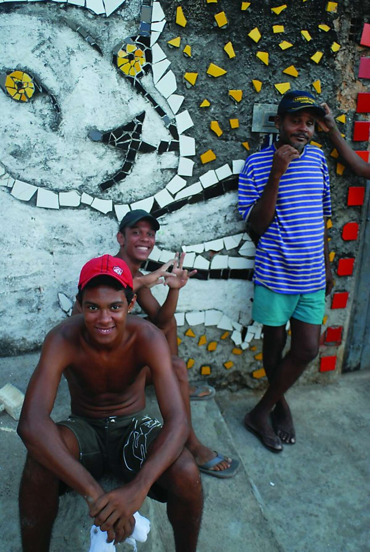 Residents of Brazilian artist Bel Borba?•s hometown, Salvador de Bahia, with his artwork, as seen in BEL BORBA AQUI, directed by Burt Sun and AndrŽ Costantini, with his work.