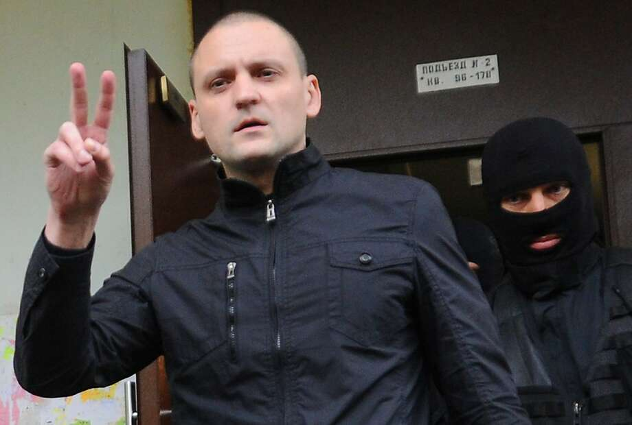 Sergei Udaltsov flashes a victory sign as he is taken in for questioning on charges of plotting riots. Photo: Andrey Smirnov, AFP/Getty Images