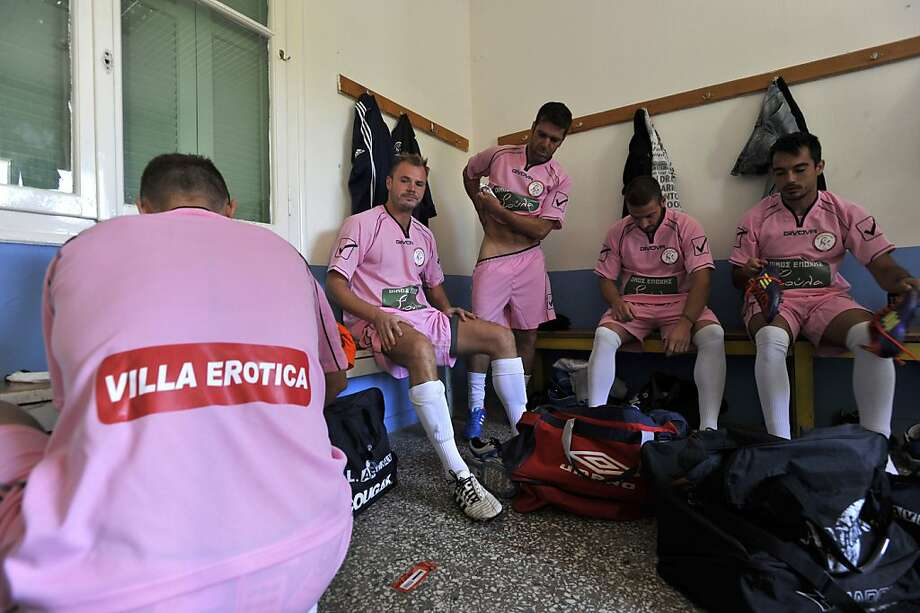 Players for Voukefalas, a small amateur soccer club, change out of their pink bordello-sponsored practice jerseys before a game in Larissa, Greece. Photo: Nikolas Giakoumidis, Associated Press