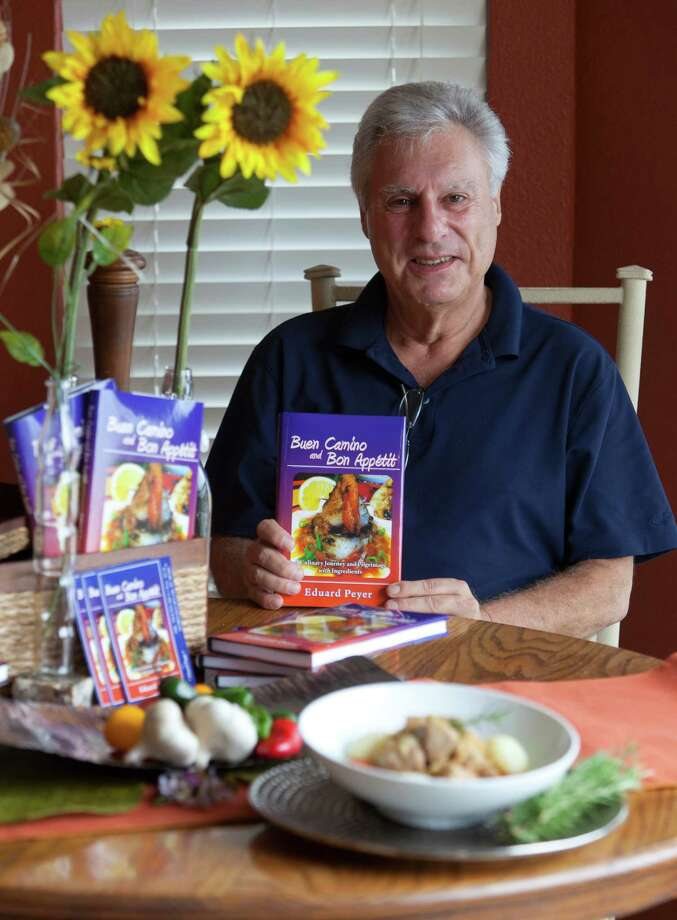 "Eddie Peyer poses Wednesday Oct. 17, 2012 with copies of his book ""Buen Camino and Bon Appetit"" and a bowl of the cabbage and pork minestrone from the book. Photo: William Luther, San Antonio Express-News / © 2012 San Antonio Express-News"