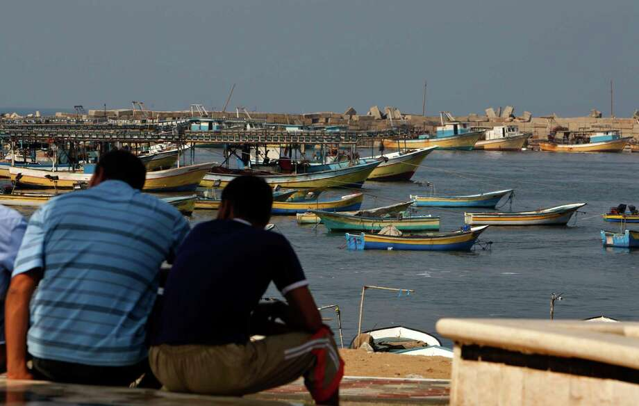 Palestinians sit by the port in Gaza City, Wednesday, Oct. 17, 2012. The Israeli military calculated the number of calories Gaza?s residents would need to consume to avoid malnutrition during a sweeping blockade imposed on the Palestinian territory between 2007 and mid-2010, according to a document the Defense Ministry released reluctantly under a court order. (AP Photo/Adel Hana) Photo: Adel Hana / AP