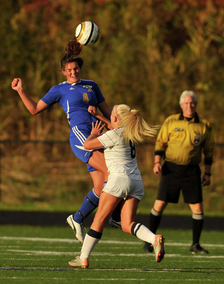 Newtown's Tressa Scott heads the ball while under pressure from Immaculate's Rachael Raffini during their game at Immaculate High School on Wednesday, Oct. 17, 2012. Immaculate won, 1-0. Photo: Jason Rearick / The News-Times