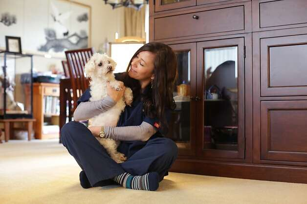 Dr. Shea Cox plays with Claire, a Maltese-poodle mix who has cancer, at the Oakland home of Jeff Aoki and Sandy Wong. Photo: Rashad Sisemore, The Chronicle