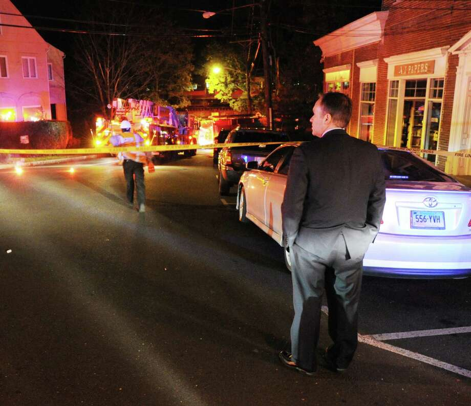 Standing on Bruce Park Avenue, Greenwich First Selectman Peter Tesei, right, views the scene of an incident in which a man suffered a severe head injury after being hit by a train along the Metro-North Railroad tracks near the Davis Drive overpass in the area of Bruce Park Avenue Extension, Greenwich, Wednesday night, Oct. 17, 2012. Photo: Bob Luckey / Greenwich Time