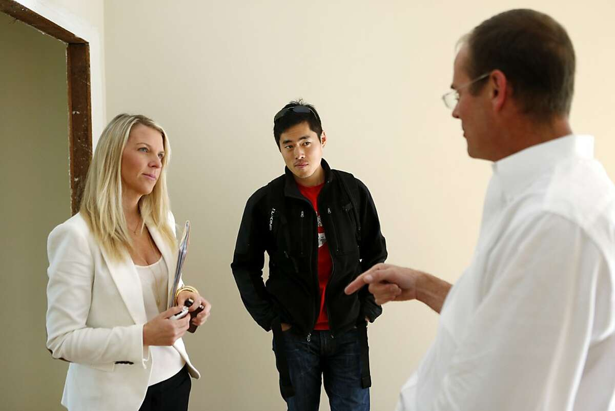 Bo Lu (center), of Seattle, is shown a one bedroom apartment by Wendy Willbanks (left), of She Moves You, and property manager Larry Feurzeig, of Gaetani Real Estate at 959 Haight Street on Wednesday, October 17, 2012 in San Francisco, Calif.