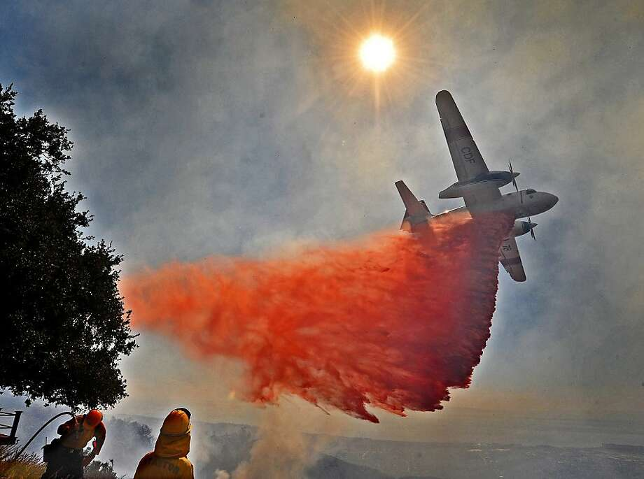 Firefighters and a fixed-wing aircraft battle a wildfire in the Painted Cave area of Santa Barbara, Calif., Wednesday, Oct. 17, 2012. The wildfire in the rugged hills overlooking Santa Barbara threatened about 100 homes in the area where a fire in 1990 killed one person and burned about 550 homes. Photo: Mike Eliason, Associated Press