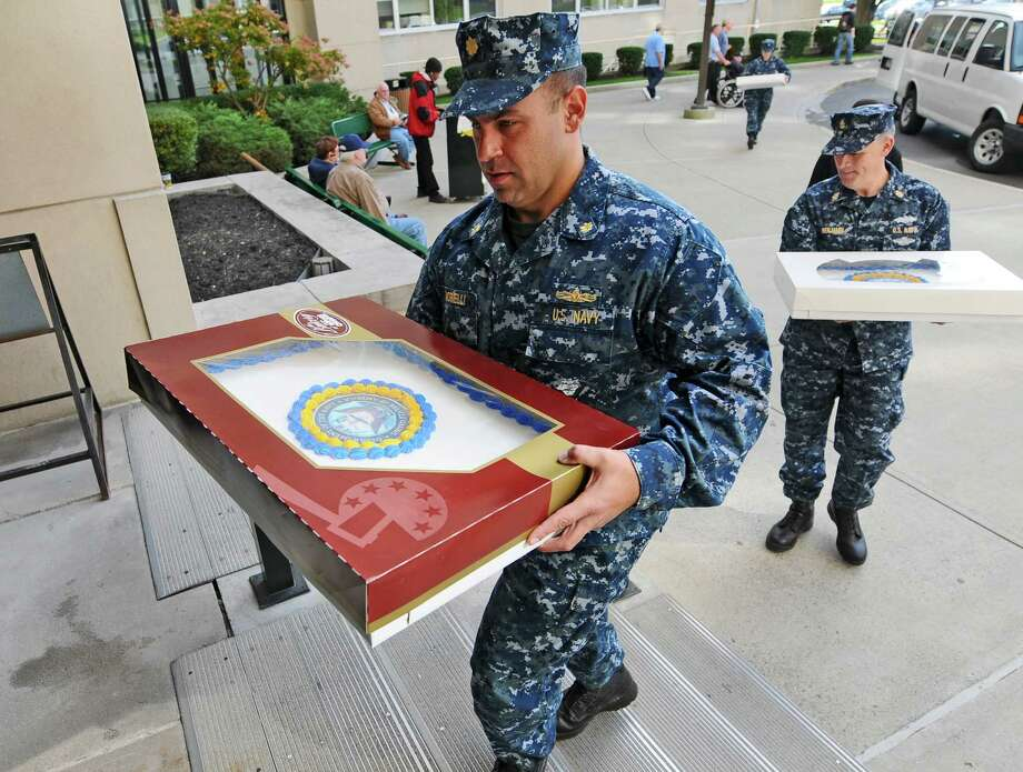 Lt. Commander Anthony Morelli, left, and Chief Petty Officer Bill Benjamin, right, and other members of the Navy Operational Support Center Glenville bring cake to be delivered to veterans, to celebrate the US Navy's 237th birthday at the Stratton VA Medical Center,  on Wednesday Oct. 17, 2012 in Albany, NY. They brought cake to veterans throughout the medical center.  (Philip Kamrass /  Times Union) Photo: Philip Kamrass / 00019715A