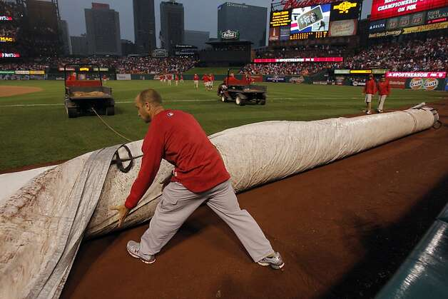 Busch Stadium personnel rolled out the tarps in the bottom of the seventh inning as the game was delayed by rain. The San Francisco Giants played the St. Louis Cardinals in Game 3 of the National League Championship Series at Busch Stadium on Wednesday, October 17, 2012, in St. Louis, Mo. Photo: Carlos Avila Gonzalez, The Chronicle