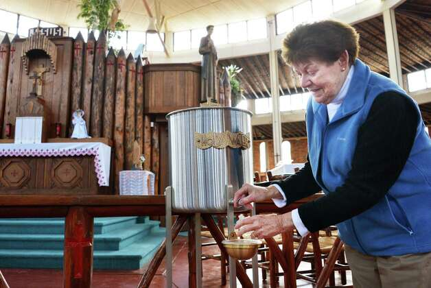 Maureen Humistan of Saratoga Springs fills a vial with holy water in the coliseum at the Shrine of Our Lady of Martyrs in Auriesville Wednesday Oct. 17, 2012.  (John Carl D'Annibale / Times Union) Photo: John Carl D'Annibale / 00019706A