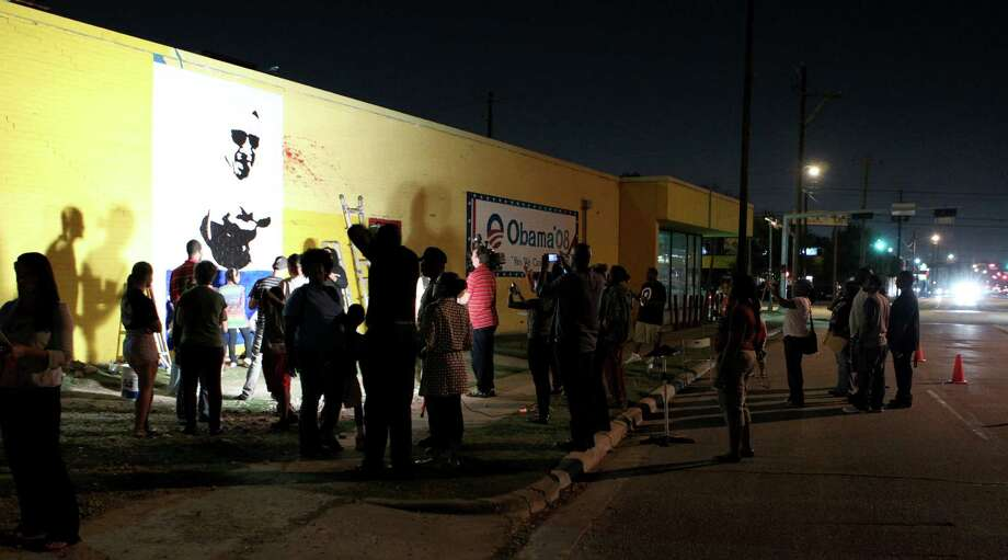 The work drew a small crowd after sundown Wednesday, Oct. 17, 2012. at the former Democratic Party headquarters. Photo: Nick De La Torre, Houston Chronicle / © 2012  Houston Chronicle