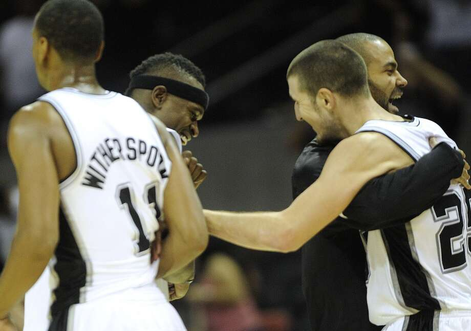 Nando De Colo of the Spurs (right) is embraced by teammate Tony Parker, who did not play and is credited with calling the final play of game during which De Colo hit a game-winning shot to beat the Atlanta Hawks at the AT&T Center on Wednesday, Oct. 10, 2012. Teammates Wesley Witherspoon and Stephen Jackson also celebrate. (Billy Calzada / San Antonio Express-News)