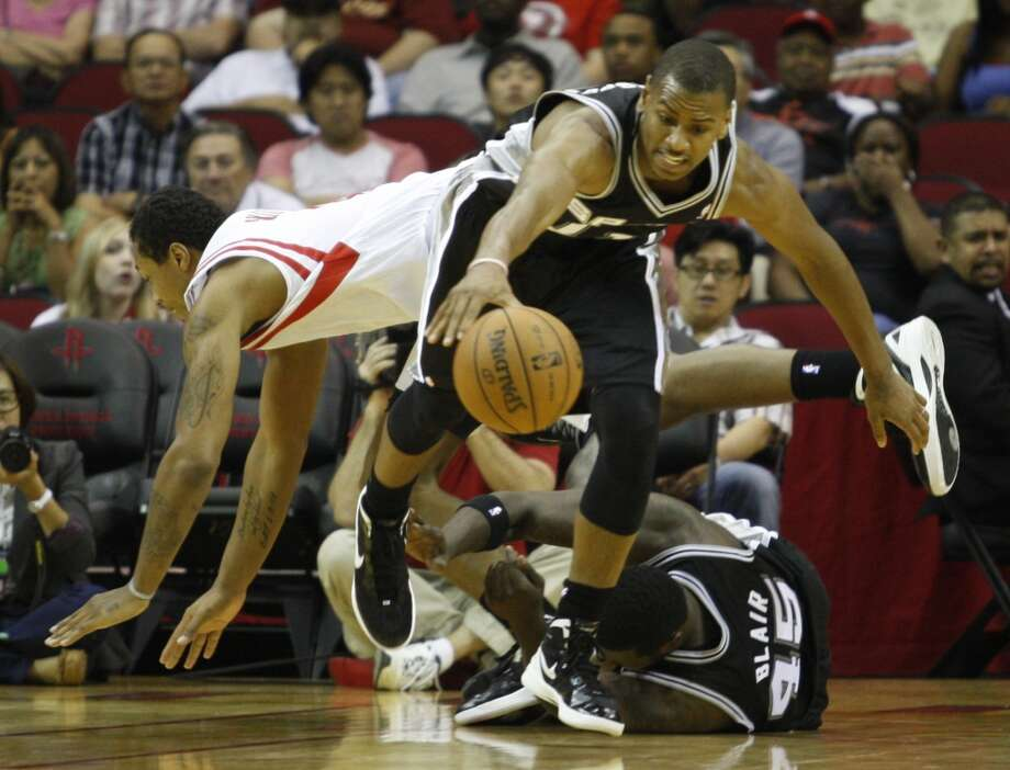 The Spurs' Wesley Witherspoon (11) dives for the ball while defended by the Houston Rockets Greg Smith (4) during the second half of an NBA basketball game, Sunday, Oct. 14, 2012, in Houston. Spurs won 116-107. (Eric Kayne / Associated Press)