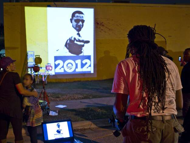 Artist Reginald Adams tries to line up a projection used for the new Obama mural, Wednesday, Oct. 17, 2012. The previous mural, also the work of Adams, was defaced by vandals across from The Breakfast Klub restaurant in Midtown.
