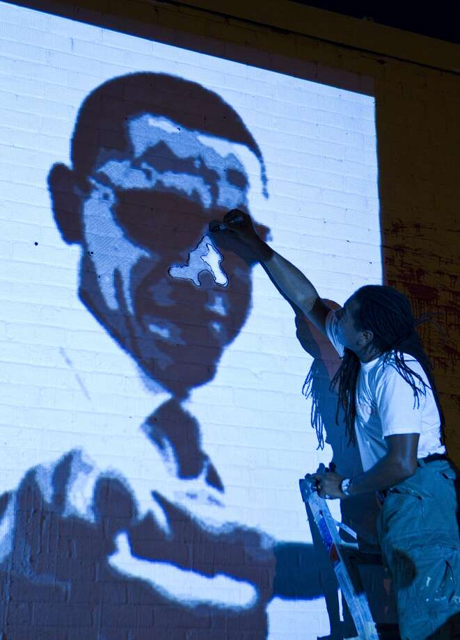 While making the mural, Adams traces the projection on the wall of the former Democratic Party headquarters, Wednesday, Oct. 17, 2012.