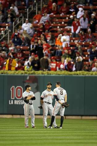 Outfielders, Gregor Blanco, left, Angel Pagan, center, and Hunter Pence, right, talk in centerfield during a pitching change after a rain delay that left most of the stands empty when play resumed. The San Francisco Giants played the St. Louis Cardinals in Game 3 of the National League Championship Series at Busch Stadium on Wednesday, October 17, 2012, in St. Louis, Mo. Photo: Carlos Avila Gonzalez, The Chronicle