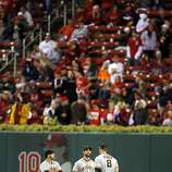 Outfielders, Gregor Blanco, left, Angel Pagan, center, and Hunter Pence, right, talk in centerfield during a pitching change after a rain delay that left most of the stands empty when play resumed. The San Francisco Giants played the St. Louis Cardinals in Game 3 of the National League Championship Series at Busch Stadium on Wednesday, October 17, 2012, in St. Louis, Mo.