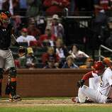 Matt Holliday rolls on the ground in pain after fouling a ball off his shin in the eighth inning. Buster Posey watches. The San Francisco Giants played the St. Louis Cardinals in Game 3 of the National League Championship Series at Busch Stadium on Wednesday, October 17, 2012, in St. Louis, Mo.