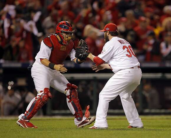 Jason Motte, right, and Yadier Molina, left, celebrate after winning the game against the Giants 3-1. The San Francisco Giants played the St. Louis Cardinals in Game 3 of the National League Championship Series at Busch Stadium on Wednesday, October 17, 2012, in St. Louis, Mo. Photo: Carlos Avila Gonzalez, The Chronicle