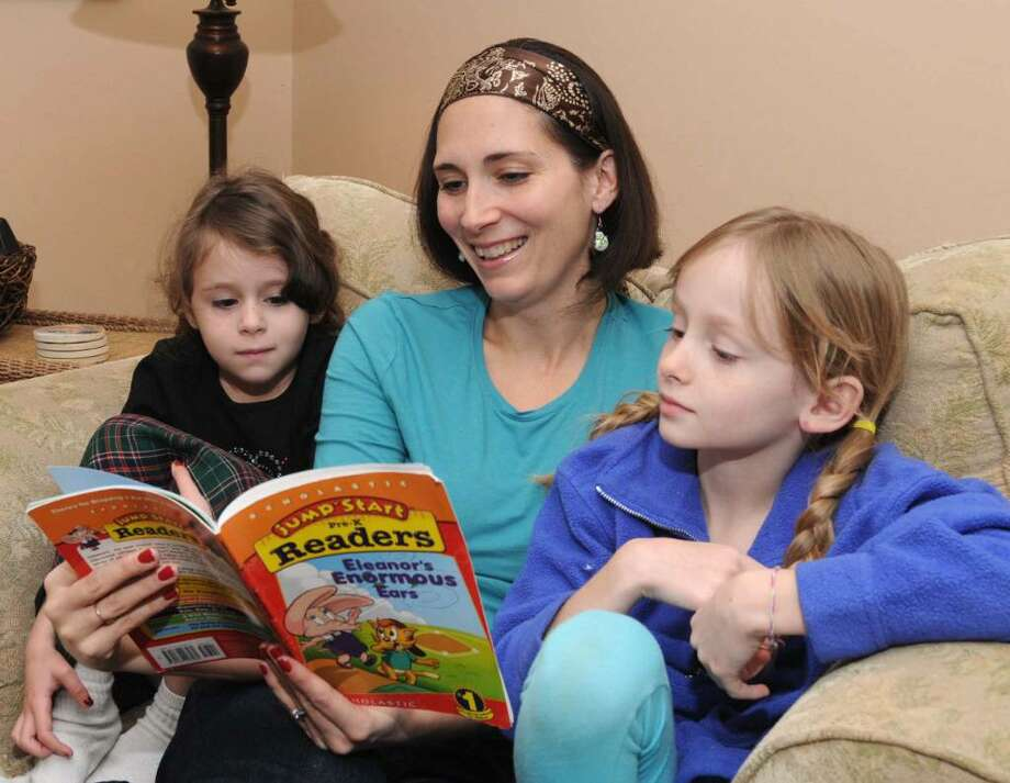 Jessica Clifford, 37, of Danbury reads a Jump Start book  to two of her four children at her home on Saturday Nov. 28, 2009. On the Left is five year old Julia and on the right is seven year old Audrey. Photo: Lisa Weir / The News-Times