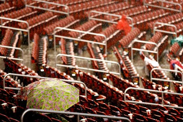 ST LOUIS, MO - OCTOBER 17:  A few fans sit in their seat during a rain delay in the seventh inning in Game Three of the National League Championship Series between the Cardinals and the San Francisco Giants at Busch Stadium on October 17, 2012 in St Louis, Missouri.  (Photo by Kevin C. Cox/Getty Images) Photo: Kevin C. Cox, Getty Images