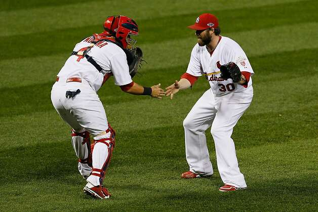 ST LOUIS, MO - OCTOBER 17:  Jason Motte #30 and catcher Yadier Molina #4 of the St. Louis Cardinals celebrate the Cardinals 3-1 victory against the San Francisco Giants in Game Three of the National League Championship Series at Busch Stadium on October 17, 2012 in St Louis, Missouri.  (Photo by Kevin C. Cox/Getty Images) Photo: Kevin C. Cox, Getty Images