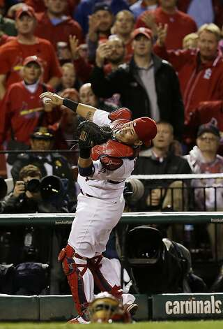 St. Louis Cardinals catcher Yadier Molina (4) reaches over to catch a fly ball hit by by San Francisco Giants' Aubrey Huff (17) during the eighth inning of Game 3 of baseball's National League championship series, Wednesday, Oct. 17, 2012, in St. Louis. (AP Photo/David J. Phillip) Photo: David J. Phillip, Associated Press