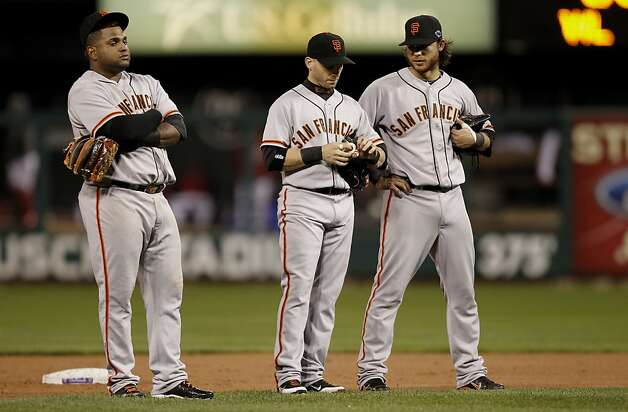 Giants' infielders, Pablo Sandoval, Marco Scutaro and Brandon Crawford gather during a pitching change in the bottom of the eighth inning, as the San Francisco Giants went on to lose to the St. Louis Cardinals 3-1 in game three, of the National League Championship Series, on Wednesday Oct. 17, 2012, at Busch Stadium in  St. Louis, Mo. Photo: Michael Macor, The Chronicle