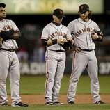 Giants' infielders, Pablo Sandoval, Marco Scutaro and Brandon Crawford gather during a pitching change in the bottom of the eighth inning, as the San Francisco Giants went on to lose to the St. Louis Cardinals 3-1 in game three, of the National League Championship Series, on Wednesday Oct. 17, 2012, at Busch Stadium in  St. Louis, Mo.