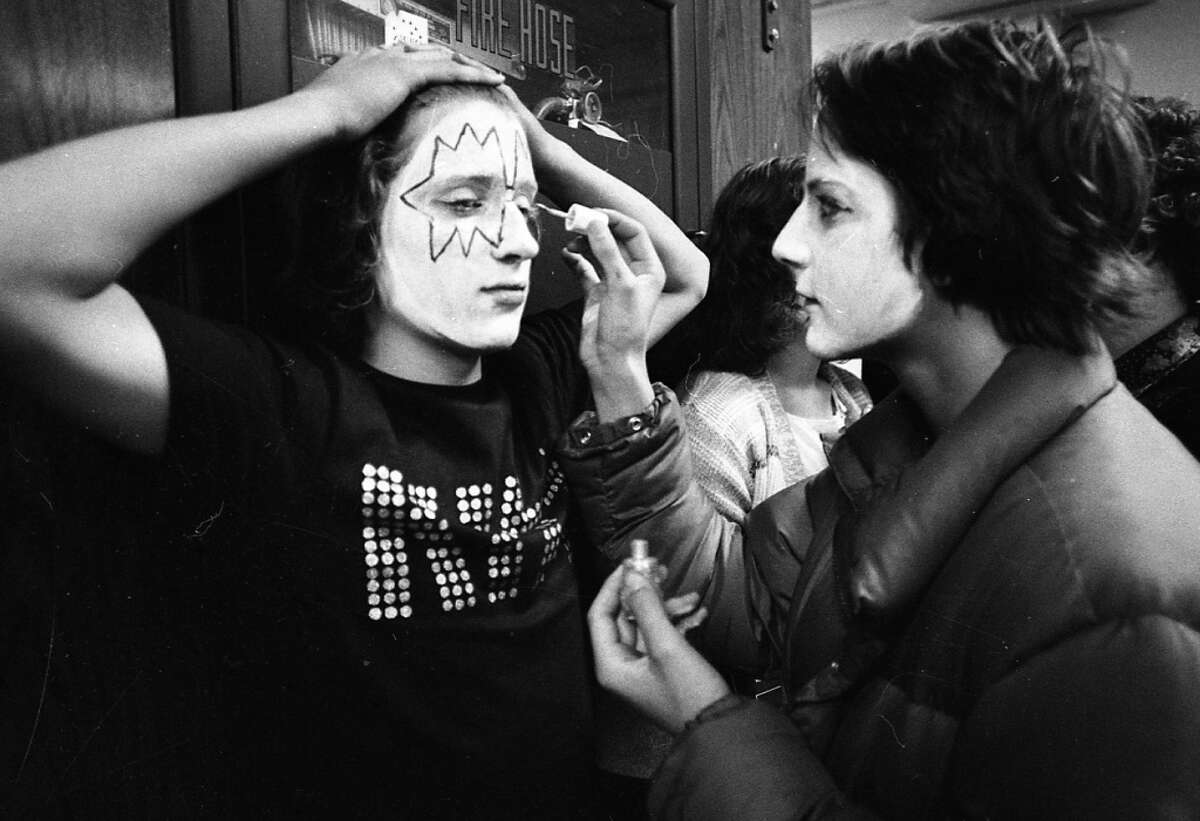 Observe the 1977 tradition of holding your hair back, while one of your buddies applies KISS makeup to your face. The guy on the right appears to be using Wite-Out. (Stephanie Maze / The Chronicle)