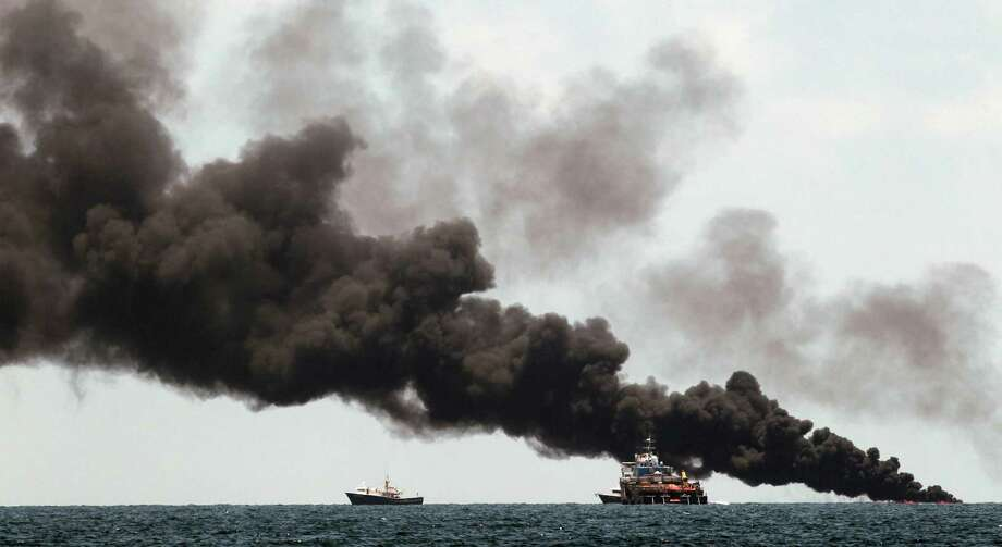 Vessels monitor a oil burn in the area of the Deepwater Horizon disaster on the Gulf of Mexico, Tuesday, July 13, 2010. BP officials have placed a containment cap over the leak in hopes that the flow of oil will be diminished. (AP Photo/Dave Martin) Photo: Dave Martin, AP / AP