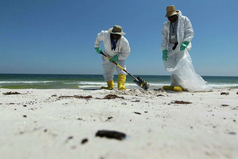GULF SHORES, AL - JUNE 08:  Workers pick up oil patches and tar that  washed up on the beach at Bon Secour National Wildlife Refuge from the Deepwater Horizon oil spill in the Gulf of Mexico on June 8, 2010 in Gulf Shores, Alabama.  Early reports indicate that BP's latest plan to stem the flow of oil from the site of the Deepwater Horizon incident may be having some success.  (Photo by Joe Raedle/Getty Images) Photo: Joe Raedle, Getty Images / Getty Images North America