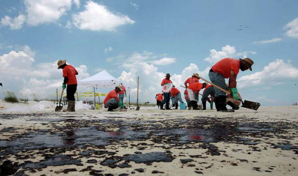 Oil cleanup workers hired by BP pick up oil on the beach in Gulf Shores, Ala., Friday, July 2, 2010.