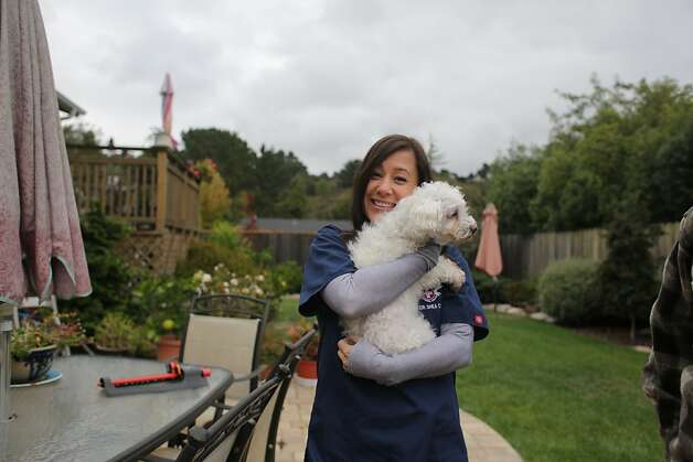 Claire, a mixed Maltese-Poodle with cancer, rests in the arms of Dr. Shea Cox at the home of her owners Jeff Aoki and Sandy Wong. Dr. Shea Cox, founder of Bridge Veterinary Service, a Pet hospice, is providing care for Claire at Jeff Aoki's and Sandy Wong's home in Oakland. Pet hospices are a growing trend, which began in the Bay Area, and draw from similar principles involved in human hospices. Photo: Rashad Sisemore, The Chronicle