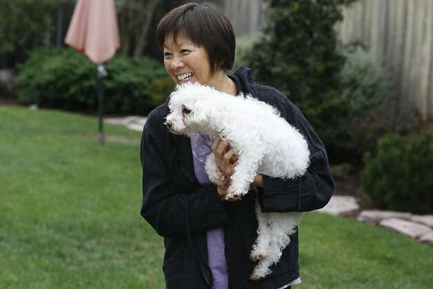 Sandy Wong plays with their dog Claire, a mixed Maltese-Poodle with cancer. Dr. Shea Cox, founder of Bridge Veterinary Service, a Pet hospice, is providing care for Claire. Pet hospices are a growing trend, which began in the Bay Area, and draw from similar principles involved in human hospice. Photo: Rashad Sisemore, The Chronicle