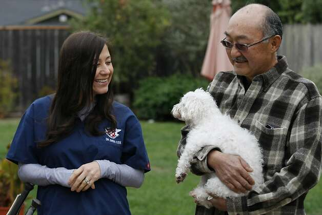 Jeff Aoki holds his dog Claire, a mixed Maltese-Poodle with cancer, while Dr. Shea Cox shares a moment of joy with Claire in the backyard of Jeff Aoki' and Sandy Wong's home. Dr. Shea Cox, founder of Bridge Veterinary Service, a Pet hospice, is providing care for Claire at the couples home in Oakland. Pet hospices are a growing trend, which began in the Bay Area, and draw from similar principles involved in human hospices. Photo: Rashad Sisemore, The Chronicle