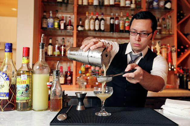 Nao's head bartender Steven Raul Martin strains ingredients for the El Matón at the restaurant on Oct. 12, 2012. Photo: Edward A. Ornelas, San Antonio Express-News / © 2012 San Antonio Express-News