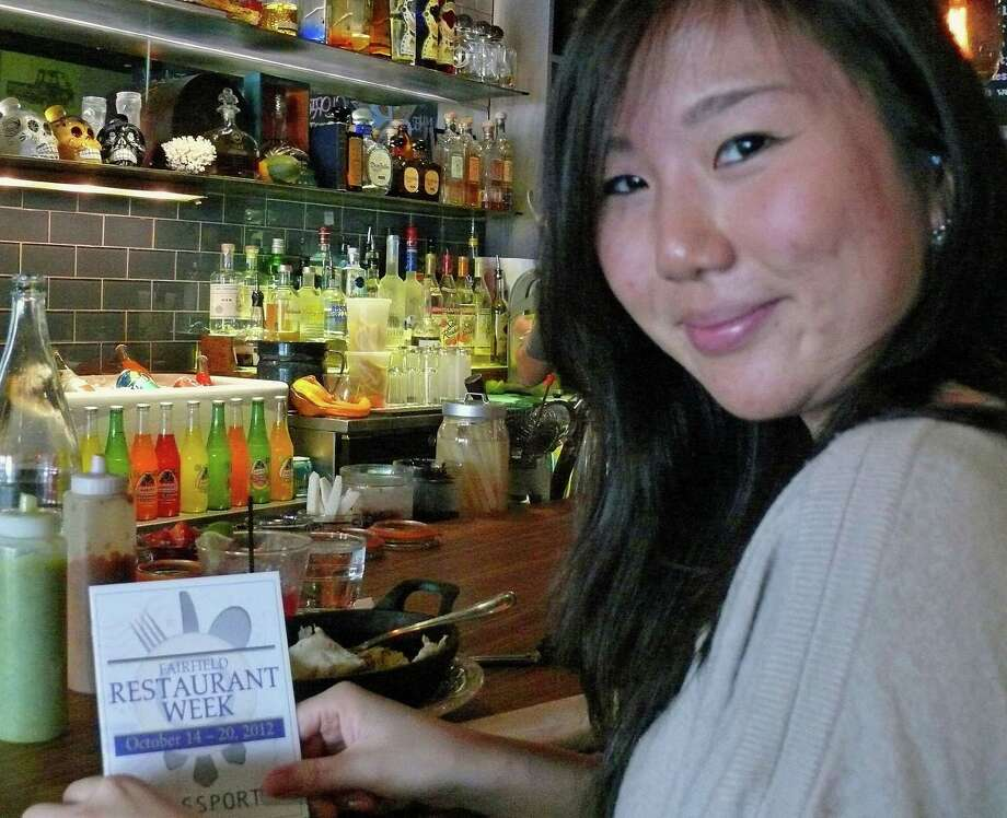 "Yukimi Harada, of Fairfield, gets her ""passport"" ready after eating at Bodega Taco Bar during Fairfield Restaurant Week. Photo: Genevieve Reilly / Fairfield Citizen"