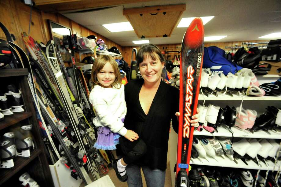 Bonnie Bianco holds her daughter, Reinna, 3, in her Newtown business, RePLAY Sports & Clothing Consignment Thursday, Oct. 18, 2012. Photo: Michael Duffy / The News-Times