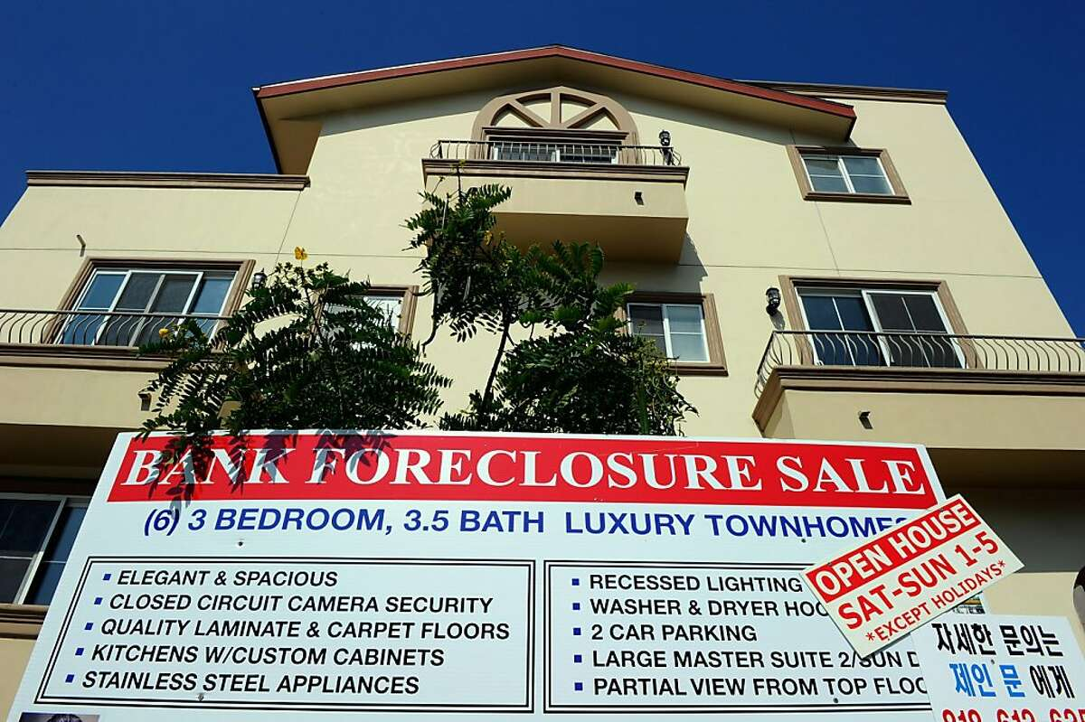 """In this file photo, A """"bank foreclosure sale"""" sign is posted in front of townhomes on in Los Angeles, California."""
