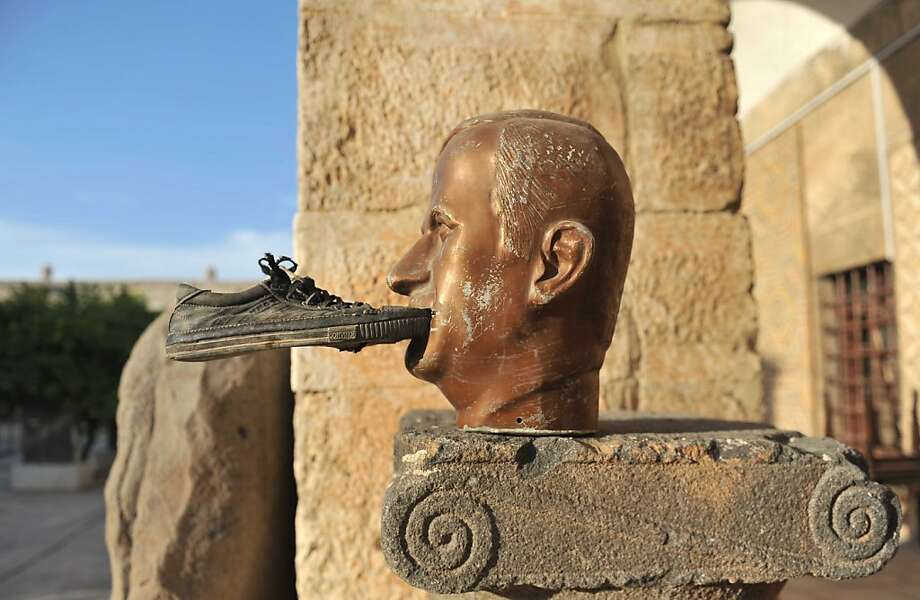 If the shoe fits:Rebels insult the memory of the late Syrian  President Hafez al-Assad with a sneaker and some Superglue  outside the  museum of Maaret al-Numan in the Idlib province. Photo: Bulent Kilic, AFP/Getty Images