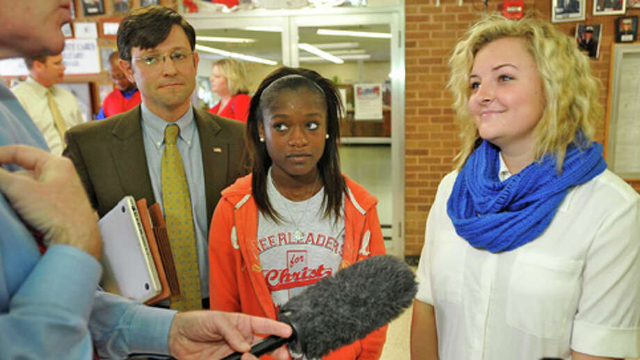 Cheerleaders Kieara Moffett, middle, and Rebekah Richardson, right, talk to the media before leaving the courthouse as Senior Counsel for the Liberty Institute, left, looks on Thursday, Oct. 18. A judge ruled Thursday that cheerleaders may continue to express their messages on banners for now. Photo: .