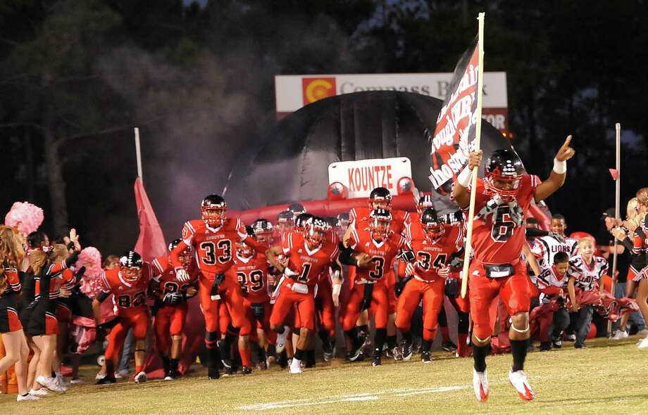 Lion #6, Jamazdon Powell, right, leads the team out onto the field in front of the home crowd. This was the first home football game in Kountze since the sign controversy started and since the Thursday hearing that determined the cheerleaders could or could not use their faith-based signs.  Kountze hasn't made the playoffs since 1973, but the team is currently 4-1after losing to Woodville Friday night October 5, 2012.  Dave Ryan/The Enterprise Photo: Dave Ryan/The Enterprise