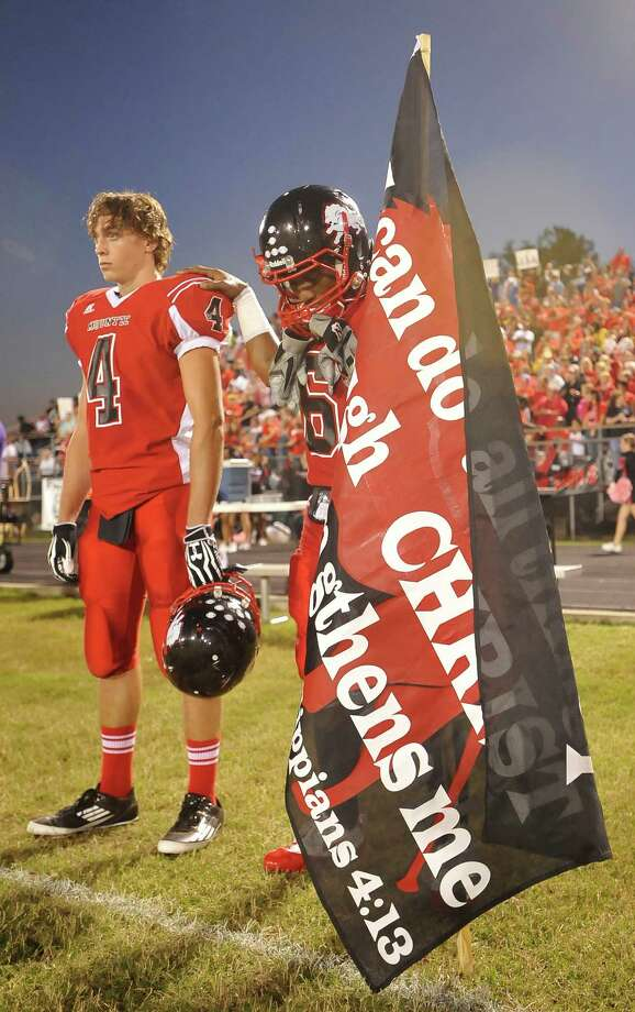 Lion #6, Jamazdon Powell right, with his hand on the shoulder of his teammate #4, Tyler Brown, bows his head before the start of the national anthem. This was the first home football game in Kountze since the sign controversy started and since the Thursday hearing that determined the cheerleaders could or could not use their faith-based signs.  Kountze hasn't made the playoffs since 1973, but the team is currently 4-1after losing to Woodville Friday night October 5, 2012.  Dave Ryan/The Enterprise Photo: Dave Ryan/The Enterprise