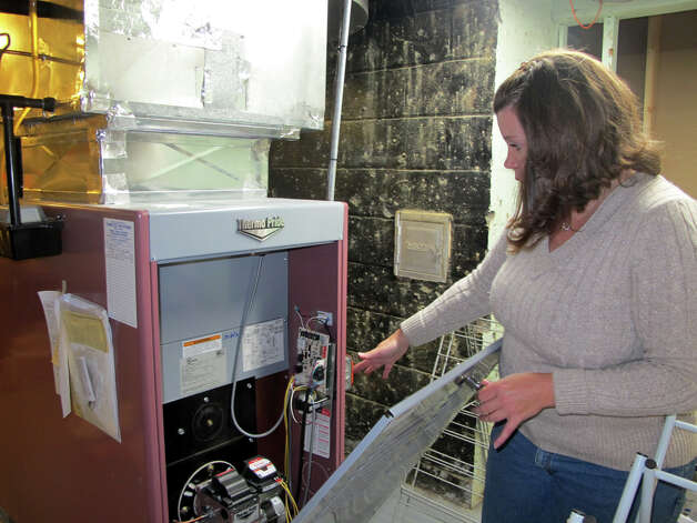 Stacy Skoldberg, of Orange, stands next to the oil furnace in her Ridgeview Road home. Skoldberg is trying to get a natural gas line installed on her street because of the high cost of heating oil. Photo: Keila Torres Ocasio / Connecticut Post