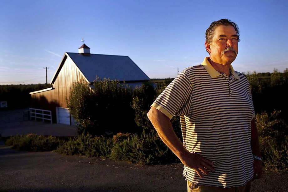Chuck Baker stands before the Baker Ranch, a 30-acre pear orchard and family heirloom on Sutter Island in the Sacramento-San Joaquin River Delta. The ranch has been in the Baker family for nearly 150 years. Photo: Arkasha Stevenson, McClatchy-Tribune News Service